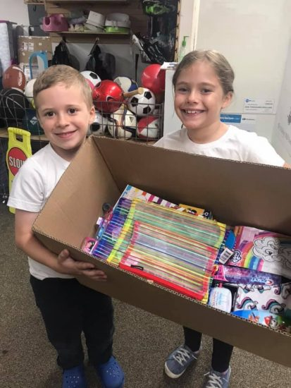 A smiling young boy and girl hold a large box between them, full of items donated for foster kids.