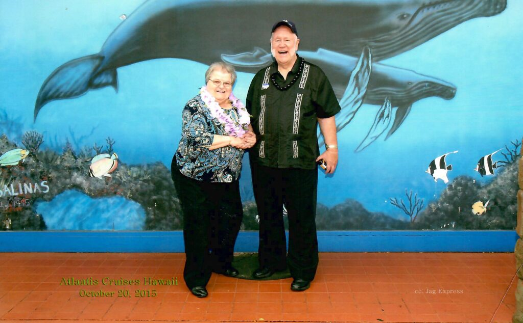 Dr. Jerry and Elaine Ramsey, wearing leis, pose on a Hawaiian cruise in front of a mural painted with whales.
