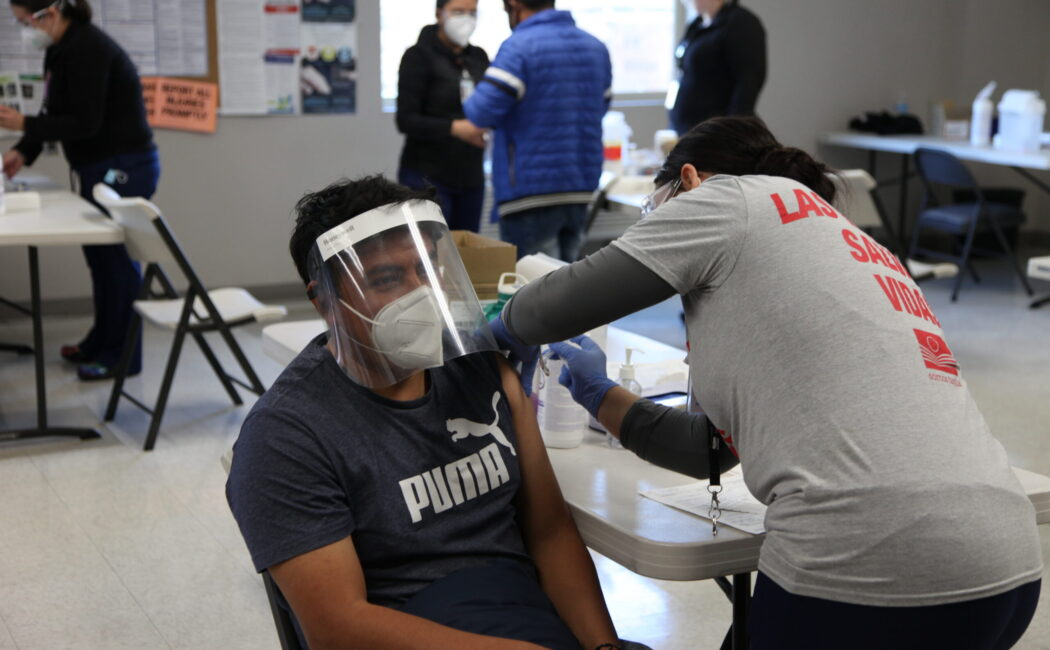 A person in a face mask and face shield receives a COVID-19 vaccine.